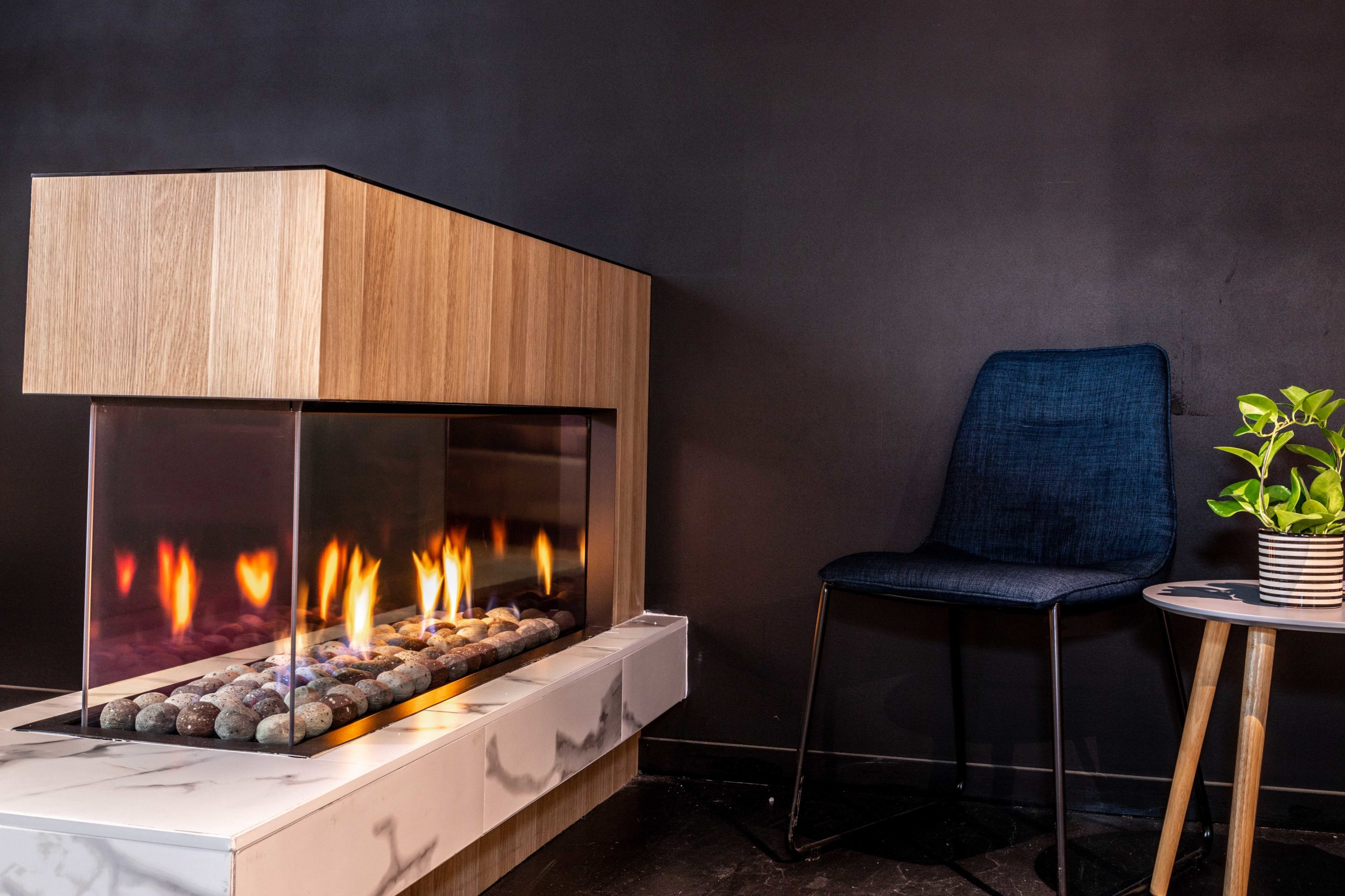 Chimney, interior wall and mantel gas log fires featured in sleek and modern stone-finished flooring on display.